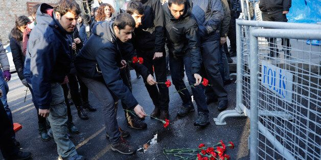 Men lay flowers outisde the Reina nightclub by the Bosphorus, which was attacked by a gunman, in Istanbul,...