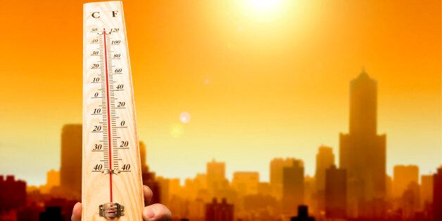 heat wave in the city and hand showing thermometer for high