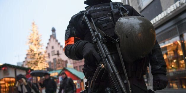 A policeman with machine gun stands guard at the Christmas market at the Roemerberg in the centre of...