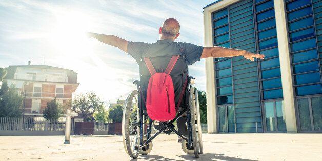 Invalid man sitting on a wheel chair and enjoying a walk