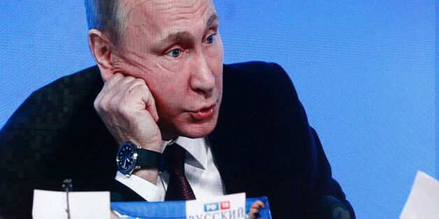 Journalists listen to Russian President Vladimir Putin during his annual end-of-year news conference...