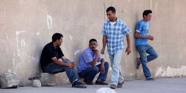 Men wait for casual work offers on a street of Cheraga, west of Algiers, June 24, 2010. Local officials...