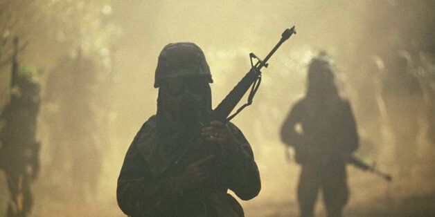 SOLDIERS IN GAS MASKS PATROLLING