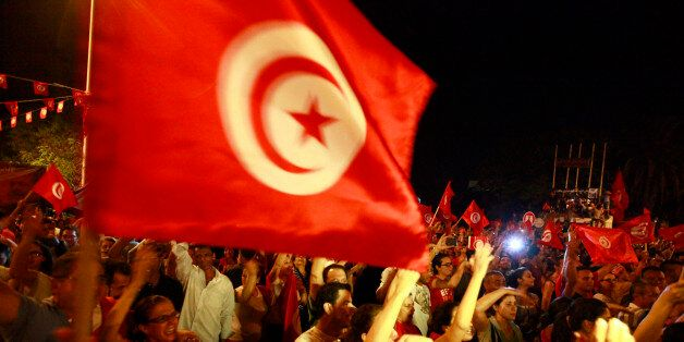 Anti-government protesters wave national flags during a demonstration in Tunis August 6, 2013. Tens of...