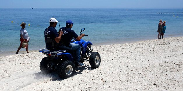Tunisian police officers patrol on a beach in front of the Imperial Marhaba Hotel in Sousse, Tunisia,...