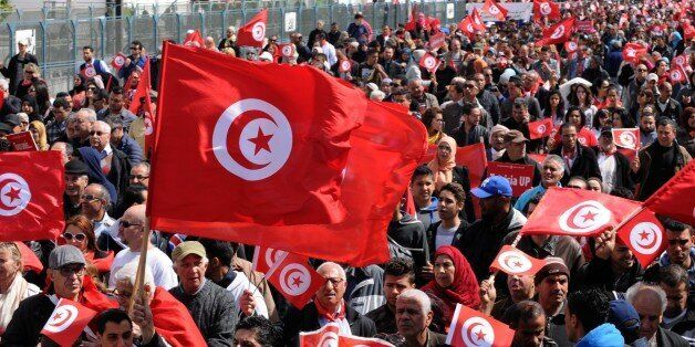 Tunisians wave their national flag and chant slogans during a march against extremism outside Tunis'...