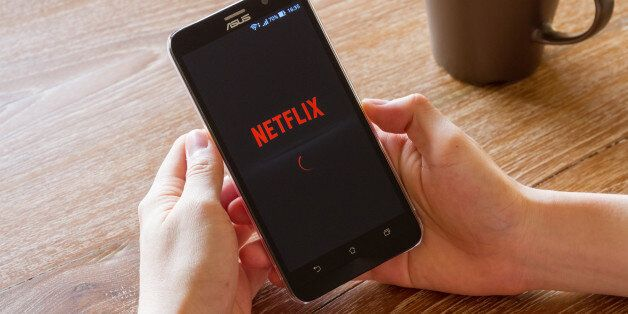Chiang Mai, Thailand - April 26, 2016: man hand holding screen shot of Netflix application showing on...