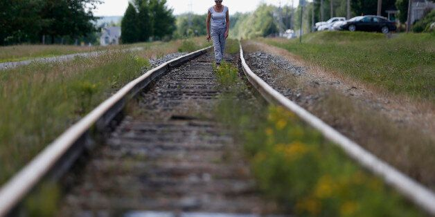 A woman walks on the railway close to the train wreck in Lac-Megantic July 13, 2013. The crude oil freight...