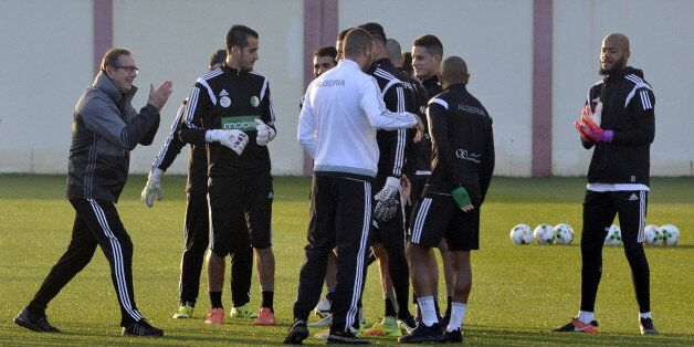 Algeria's Belgian coach George Leekens (L) applauds next to his players during a training session on...