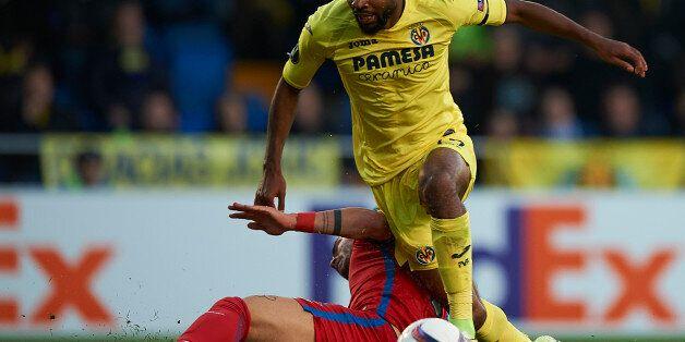 VILLARREAL, SPAIN - DECEMBER 08: Cedric Bakambu (L) of Villarreal is tackled by Alin Tosca of Steaua...