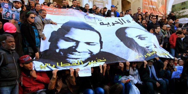 People pose around a poster of journalists Nadhir Ktari (L, in poster) and Sofiane Chourabi, who went...