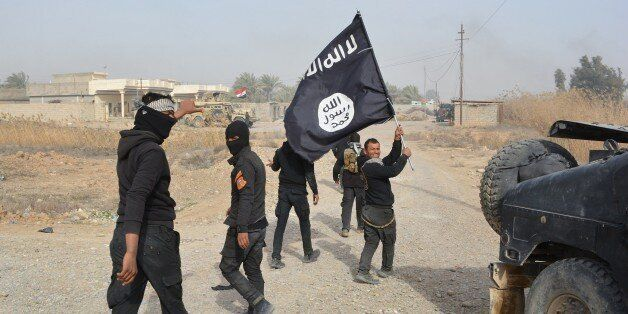 Iraqi government forces celebrate while holding an Islamis Sate (IS) group flag after they claimed they...