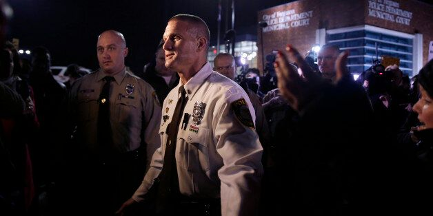 St. Louis Police Department Lt. Jerry Lohr, front, walks through a crowd of protesters trying to get...