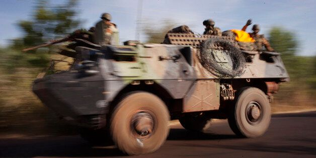 French troops ride on an amoured vehicle on a road near the frontline in their conflict with Islamists...