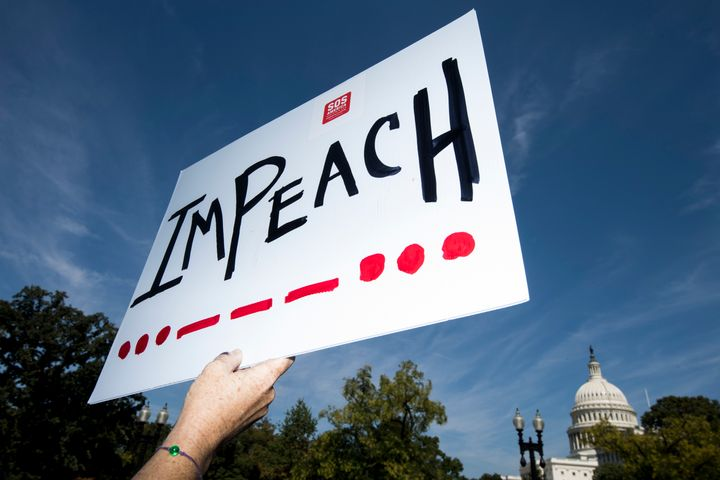 UNITED STATES - SEPTEMBER 23: A woman holds an impeach sign as Rep. Al Green, D-Texas, and Rep. Rashida Tlaib, D-Mich., speak