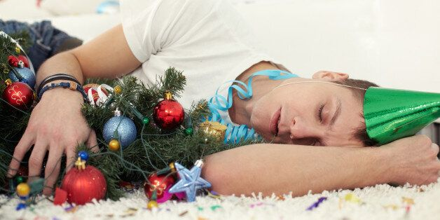 Young drunken man sleeping on floor with Christmas tree and in party