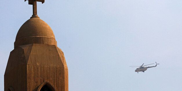 A military helicopter flies above the Virgin Mary church during the funeral for victims killed in the...