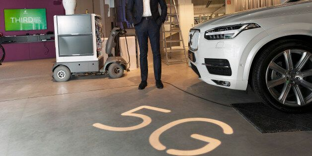 Hans Vestberg, chief executive officer of Ericsson AB, poses for a photograph beside a 5G base station...