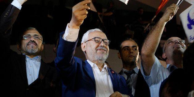Rached Ghannouchi, leader of the Islamist party Ennahda, waves the party flag outside Ennahda's headquarters...