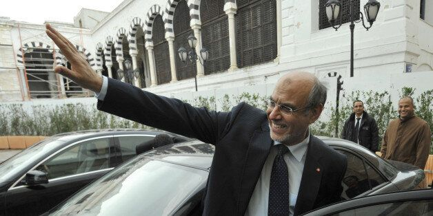 Outgoing Tunisian Prime Minister Hamadi Jebali waves to journalists at the end of the government handover...