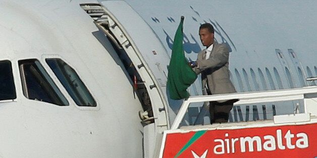 One of the hijackers of a Libyan Afriqiyah Airways Airbus A320 waves a Gaddafi-era Libyan flag at Malta...