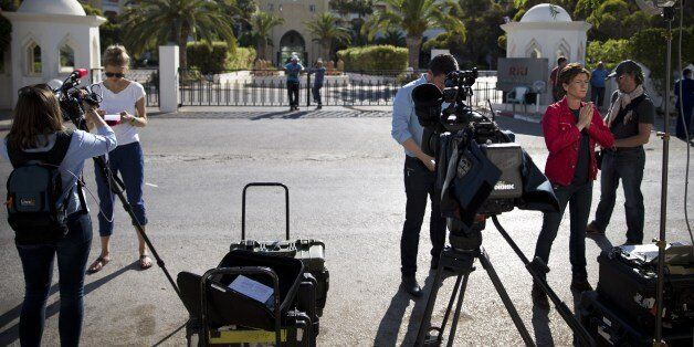 Journalists stand in front of the Riu Imperial Marhaba Hotel in Port el Kantaoui, on the outskirts of...