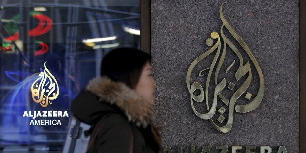 A woman passes by the Al Jazeera America broadcast center in midtown Manhattan in New York City January...