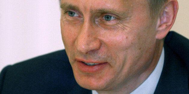Russian President Vladimir Putin speaks [to German Chancellor Gerhard Schroeder during their meeting]...