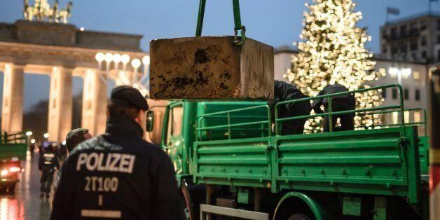 Policemen install a concrete barricade near the Brandenburg Gate in Berlin on December 22, 2016.The Berlin...