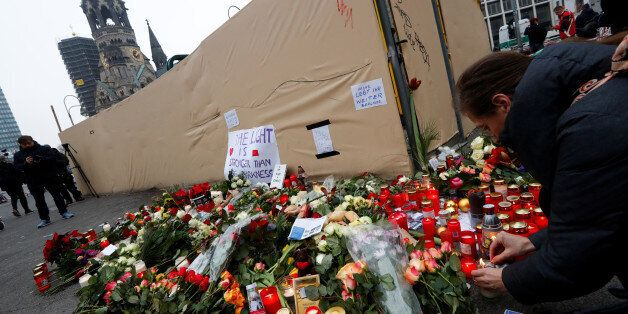 Flowers and posters are placed at the scene where a truck ploughed into a crowded Christmas market in...