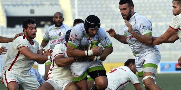 Algerian player (C) is tackled by Tunisian players during their friendly rugby match, Alegria's first...