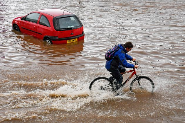 A man cycles past a stranded car on a flooded road in Birmingham city centre. The Met Office has issued...