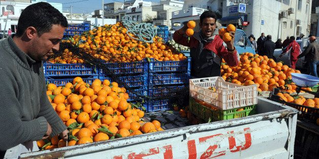 TO GO WITH AFP STORY BY Sonia BAKARICTunisian vendors sell oranges at the market in Ettadhamen, a popular...