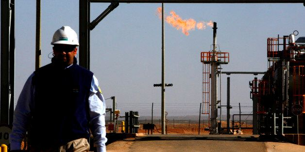 ALGERIA - DECEMBER 14: An employee walks in front of a gas flare at the In Salah Gas (ISG) Krechba Project,...