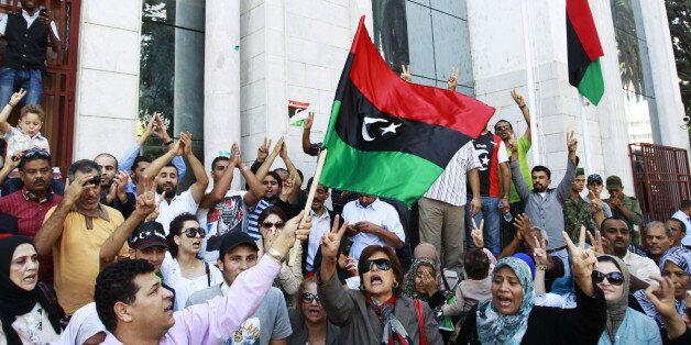 Libyan refugees in Tunisia celebrate after hearing news that Libyan leader Muammar Gaddafi was killed...