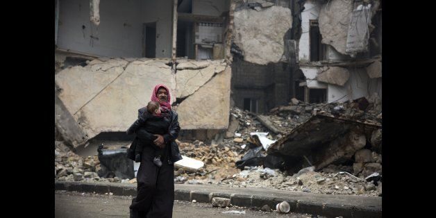 Syrians leave a rebel-held area of Aleppo towards the government-held side on December 13, 2016 during...