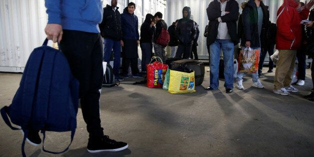 Migrants wait for a bus to leave the reception center for migrants and refugees near porte de La Chapelle...