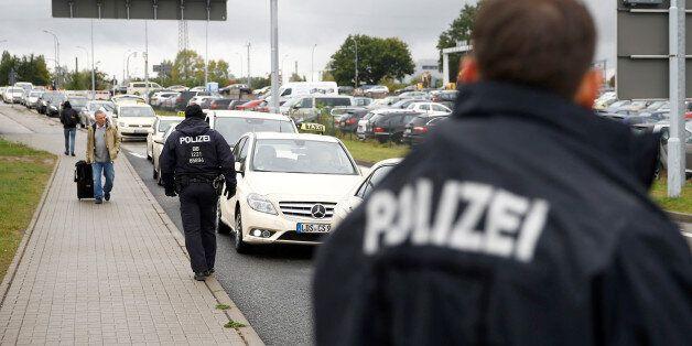 German policemen check cars on the entrance to Berlin-Schoenefeld airport, in Schoenefeld, near Berlin,...