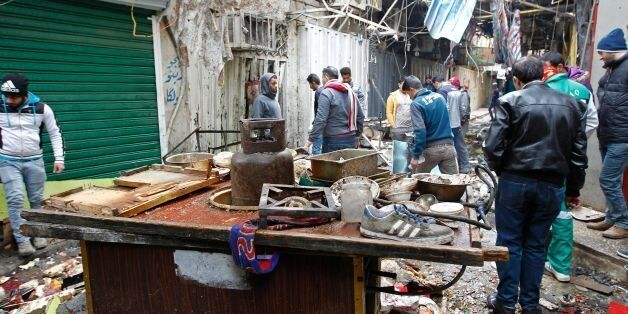 Iraqis look at the aftermath following a double bomb attack in a busy market area in Baghdad's central...