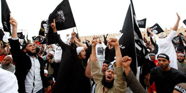 Tunisian Salafi Islamists wave flags inscribed with Islamic verses as they attend a rally in the central...