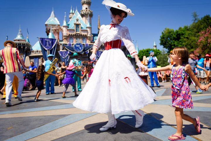 Mary Poppins smiles at a young child as she leads a line of children in song and dance in front of Cinderella's castle during Disney's 60th Diamond Celebration.