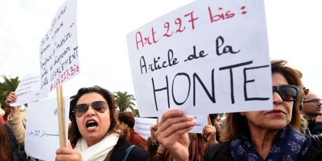 Tunisian women hold placards during a demonstration against the article 227 bis of the penal code on...