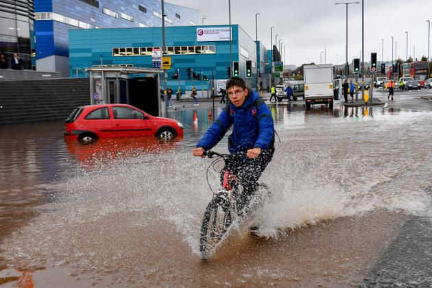 A man cycles through a flooded road in Birmingham city centre. The Met Office has issued a yellow weather...