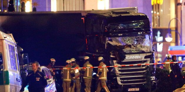 Police and emergency workers stand next to a crashed truck at the site of an accident at a Christmas...