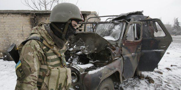 DONETSK, UKRAINE - FEBRUARY 16: An Ukrainian soldier stands next to a destroyed military vehicle of Ukrainian...