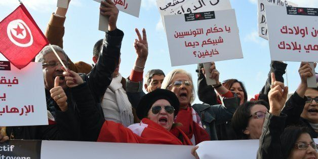 Tunisians shout slogans during a demonstration outside parliament against allowing Tunisians who joined...