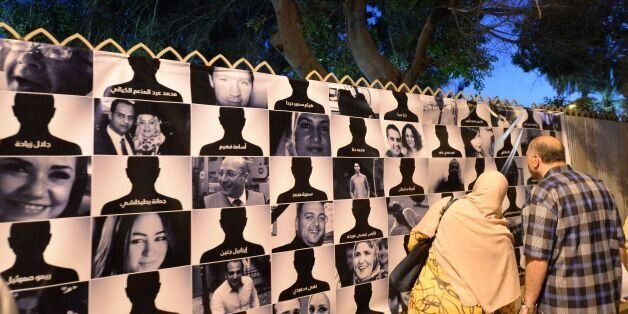 Egyptians look at posters of the 66 victims of the EgyptAir MS804 flight that crashed in the Mediterranean...