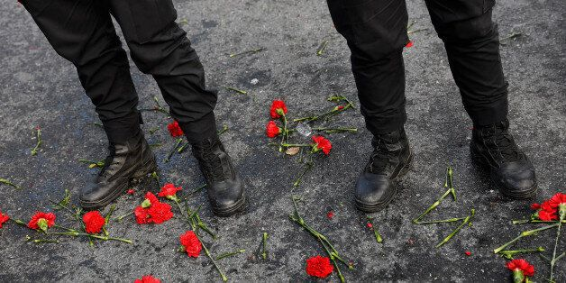 Flowers are placed next to Turkish police officers as they stand guard near the Reina nightclub, which...