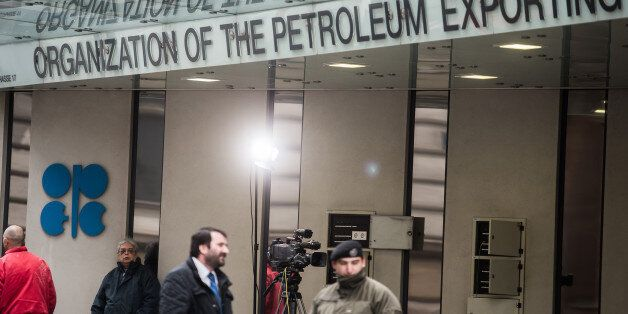 An OPEC logo sits on the wall as security and media stand outside of the OPEC Secretariat ahead of the...