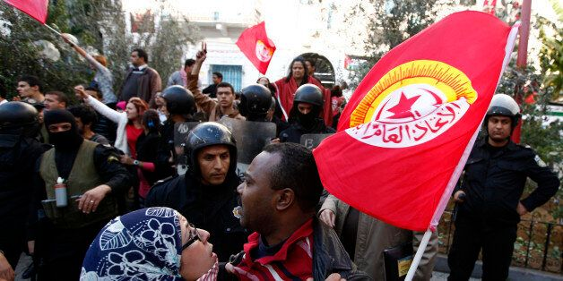 A member of main labour union body UGTT is held back during a clash between main labour union body UGTT...